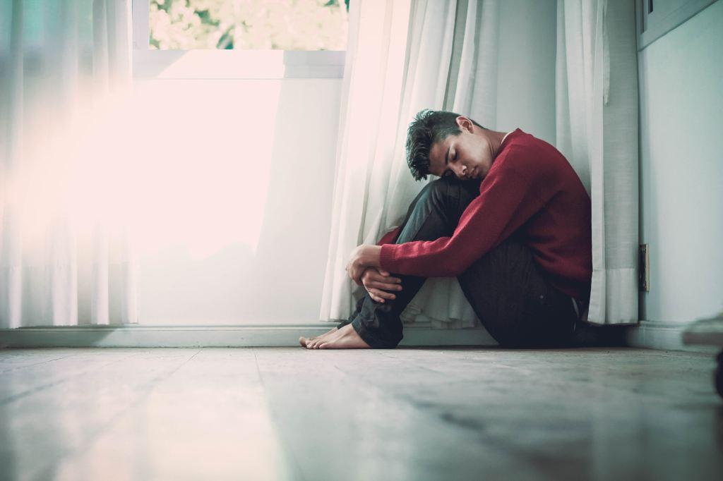 joven conansiedad se abraza las rodillas para reconfortarse.