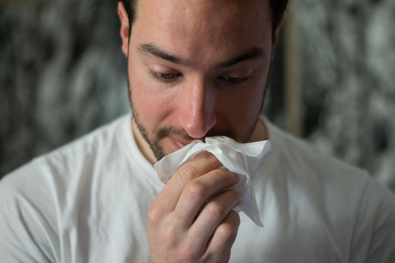 Hombre con rinitis alérgica sonándose la nariz en acupuntura valencia